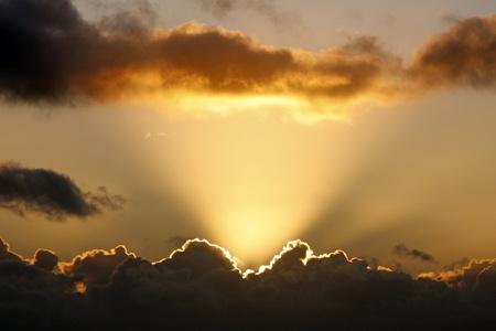 Raggi del sole e le nuvole scure al tramonto