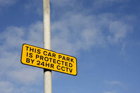 Car park CCTV sign against a blue sky photo