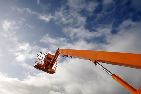 Hydraulic lift machine against a blue sky