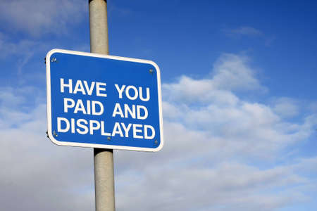 Pay and Display sign against a blue sky