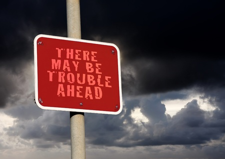 Trouble ahead sign against a dark cloud background photo