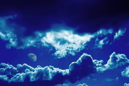 Dramatic dark blue clouds and moon background photo
