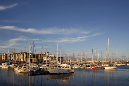Yachts and boats in a marina at sunset photo