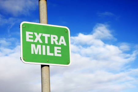 mile: Green extra mile sign against a blue sky Stock Photo