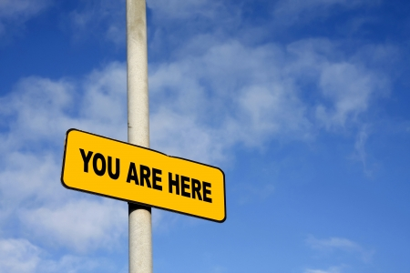 Yellow You Are Here sign against a blue sky Stock Photo