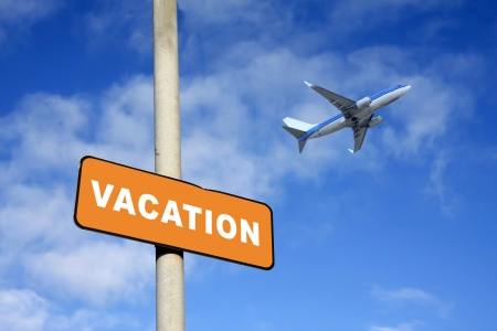 Vacation sign and plane against a blue sky