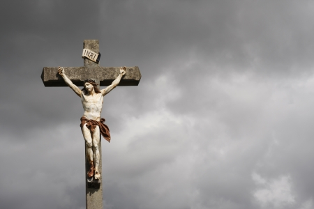 Jesus Christ crucifixion sculpture against dark clouds photo
