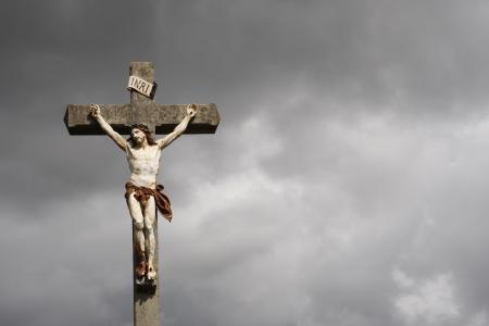 Jesus Christ crucifixion sculpture against dark clouds