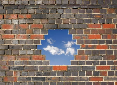 Blue sky through a hole in a brick wall photo