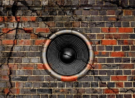 Audio speaker on a cracked brick wall background
