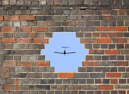 Small plane through a hole in a brick wall background