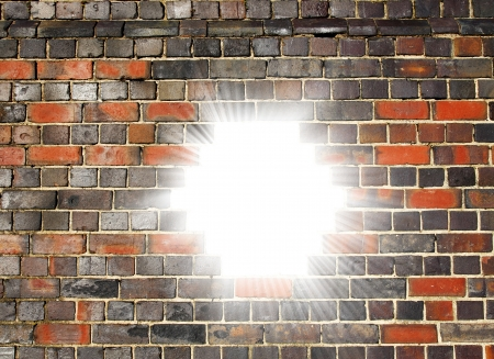 way out: White light bursting through a hole in a brick wall