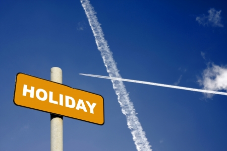 Holiday sign with jet trails crossing in a dark blue sky