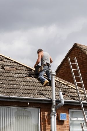 Workman repairing the ridge tiles on a roof Stock Photo