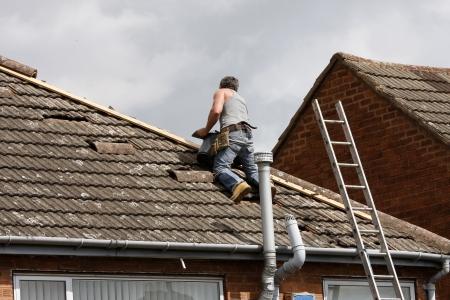 Workman repairing the ridge tiles on a roof Standard-Bild