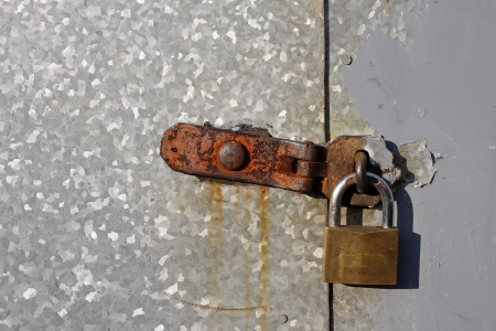 Steel doors securely locked with a rusty padlock Stock Photo - 17954117