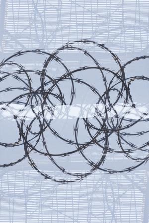 razor wire: Razor wire against a light blue background Stock Photo