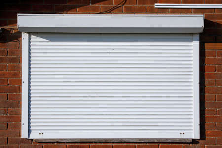 security shutters: Closed serving hatch security shutters with brick background