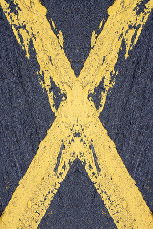 Painted yellow cross on a road photo