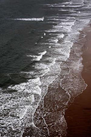 Waves breaking on a sandy beach from a high viewpoint Reklamní fotografie