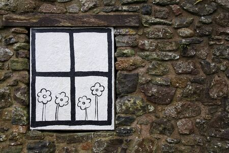 abandoned house: Cartoon window with flowers painted over a boarded up window Stock Photo