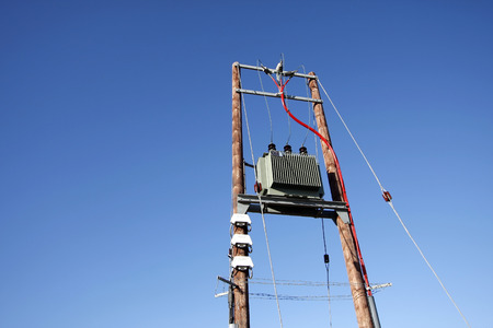 isolator insulator: Electric transformer substation against a blue sky