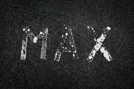 The word max, worn and faded, painted in white on a tarmac road
