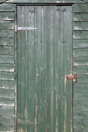 worn structure: A green weathered locked shed door