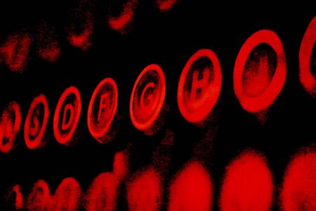 Red grunge antique typewriter keys on a black background