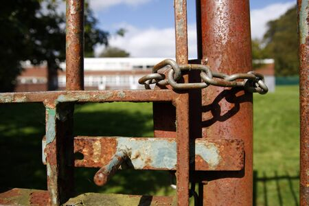 Rusty school gate chained and locked Stock Photo