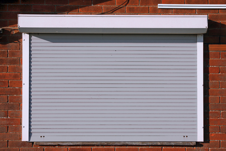 Closed light grey serving hatch security shutters with brick background