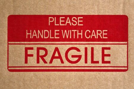 Message saying Fragile, Handle with Care on brown cardboard shipping box