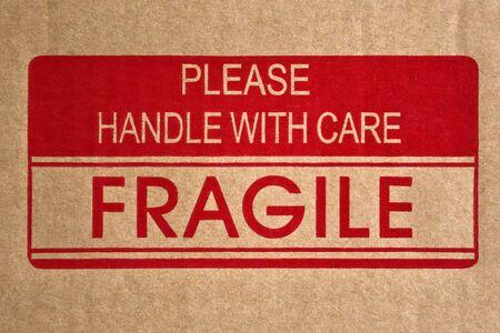 Nachricht mit der Aufschrift Zerbrechlich, mit Sorgfalt behandeln auf braunem Versandkarton Standard-Bild