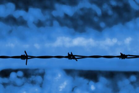 Barbed wire silhouetted against a blue background Stok Fotoğraf