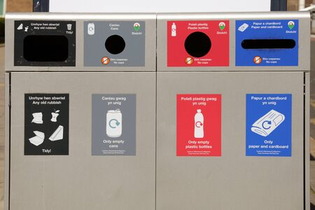 Public recycling bins with compartments for rubbish, cans, bottles, paper and cardboard. English and Welsh language.