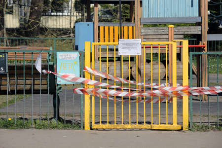 Swansea, Wales, UK - April 5, 2020: Closed outdoor play area. Children's play area locked gate with red and white tape to stop people gathering. Coronavirus social distancing quarantine.