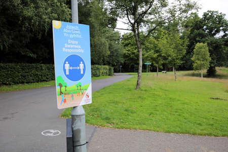 Swansea, Wales, UK - July 10, 2020: Coronavirus Covid 19 social distancing sign on a lampost in Singleton park