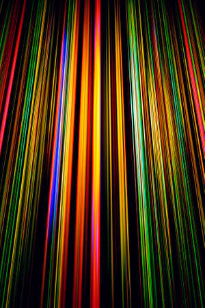Colourful light beams on a black background