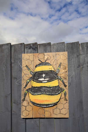 Painted bee with wire wings mounted on a wooden fence