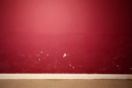 Red interior wall damaged by damp