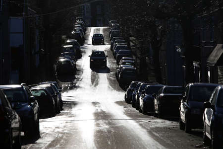Swansea, Wales, UK - December 6, 2020, tree lined city street full of parked cars, high contrast Standard-Bild
