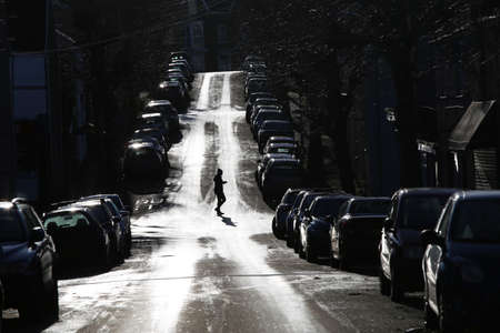 Swansea, Wales, UK - December 6, 2020, city street full of parked cars with pedestrian walking across the road, high contrast