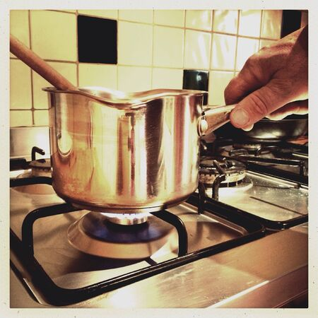 steel: Male hand holding a stainless steel saucepan over a gas flame on a cooker