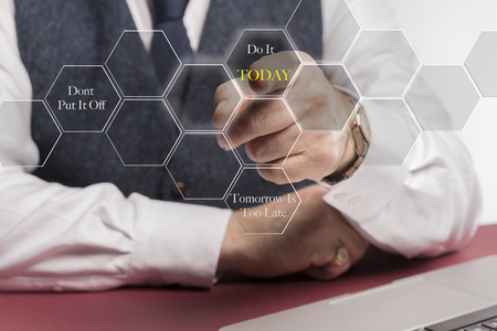 """A smartly dressed business man sitting at a desk whilst pushing a virtual button on the screen saying """" dont put ot off, do it today,  tomorrow is too late """" Stockfoto"""