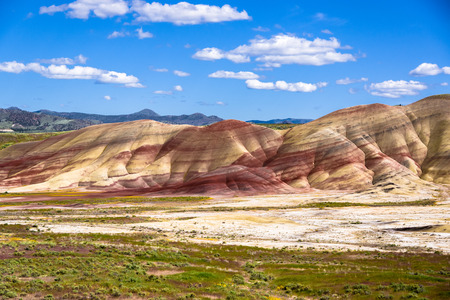 The Oregon Painted Hills. Bold red sandy soil makes stripes through the hills, alternating red, black and tan layers.