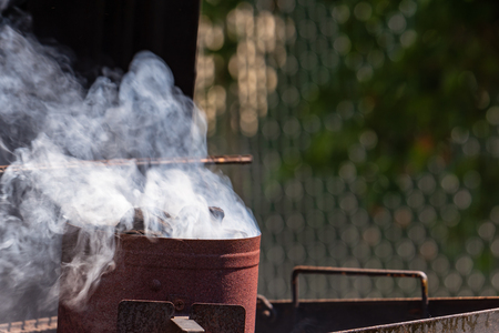 Charcoal starts smoking in a chimney starter for a barbecue.