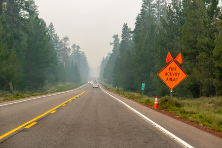 Wildfire smoke filled highway in Southern Oregon, sign at roadside
