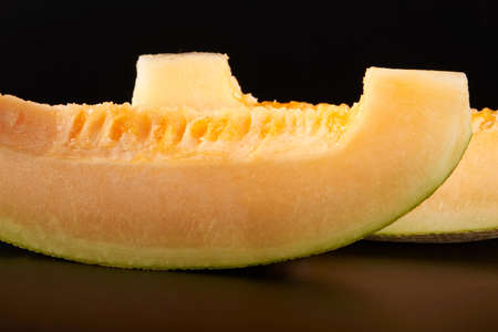 Close-up of two golden and juicy pieces of Hami melon