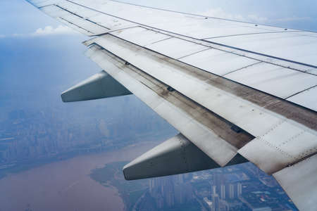 Airplane flap closeup and aerial city view