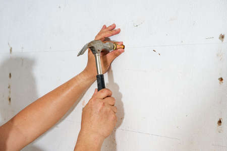 A worker is hitting a screw on the wall with a hammer